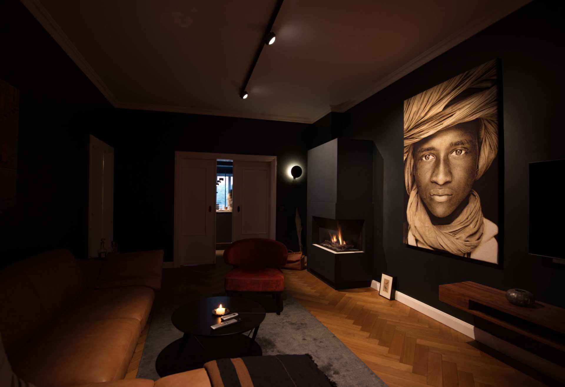 Lichtwirkung trifft schwarzen Raum mit dunklen und edlen Wänden, wenig Tageslicht und Kunstbildern im Wohnzimmer